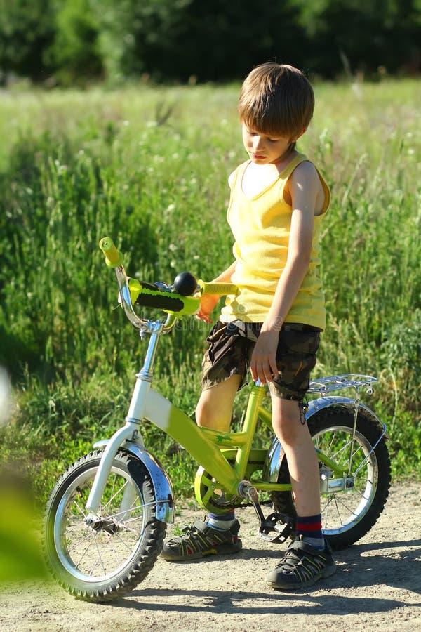 Беспристрастный портрет расстроенного мальчика с велосипедом в sunlit поле стоковое изображение