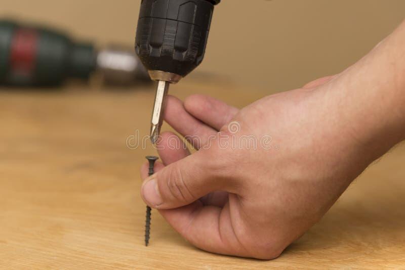 Беспроволочная отвертка в руках человека, на деревянной предпосылке, тема работы ремонта стоковое фото rf