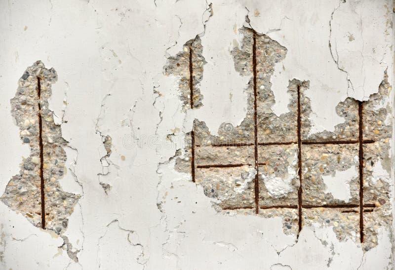 Бетонная стена с проламываниями и видимая арматура как предпосылка стоковые фото