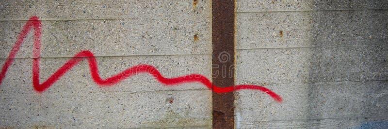 Бетонная стена с трассировкой красной краски стоковые изображения rf