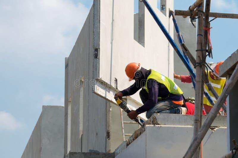 Бетонная стена электрического сверлильного аппарата пользы рабочий-строителя сверля в районе конструкции, Precast конструкции дом стоковые фотографии rf