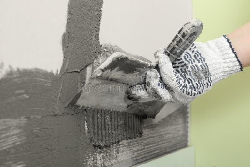 Бетон работника распространяя на стене со шпателем Кафельная установка стоковое изображение