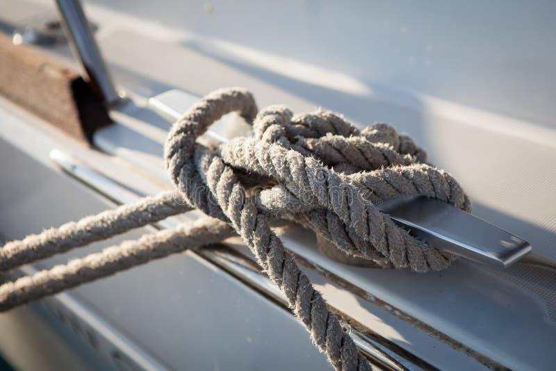 Белая веревочка зачаливания связанная вокруг стального анкера на шлюпке или корабле стоковое изображение