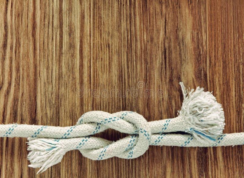 Белая веревочка с морским узлом рифа на предпосылке w grunge деревянной стоковая фотография rf
