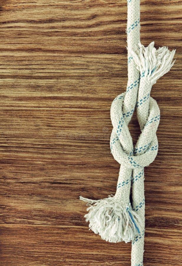 Белая веревочка с морским узлом рифа на предпосылке w grunge деревянной стоковые изображения