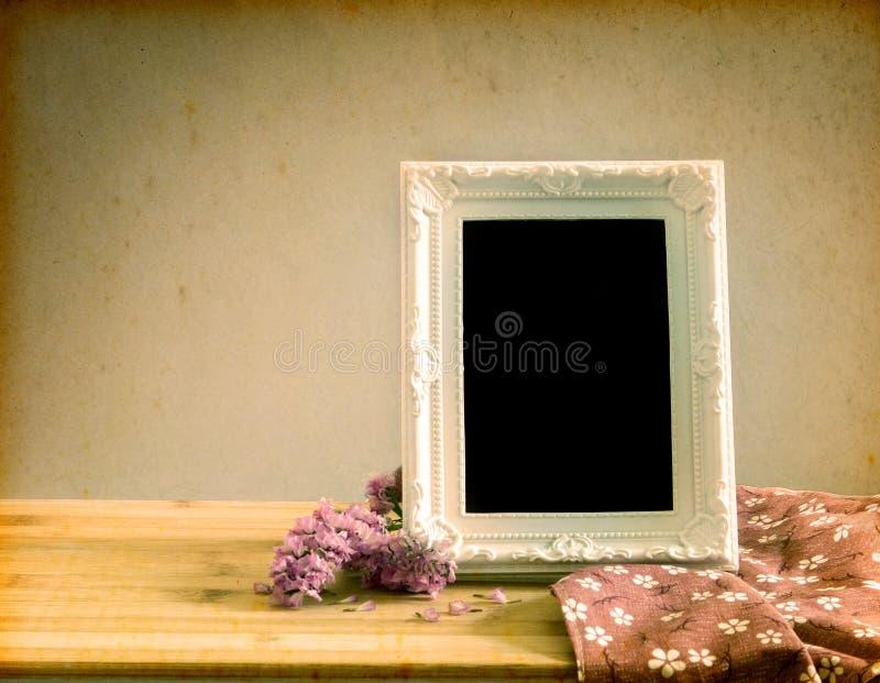 Белая винтажная рамка фото с сладостным цветком statice на деревянном t стоковое фото