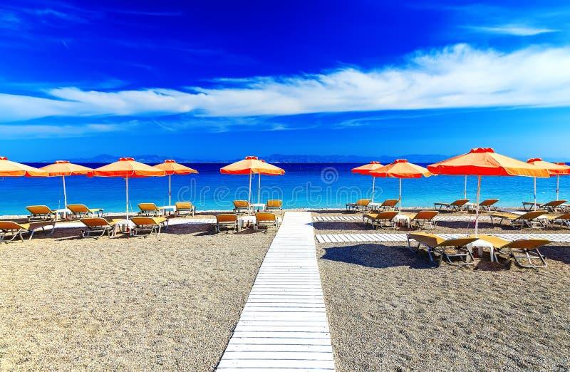 Белая деревянная дорожка на пляже включая зонтики с шезлонгами Эгейское море Греция Родос каек пляжа стоковая фотография rf