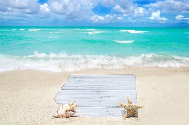 Белая деревянная доска с seashell и морские звёзды на песчаном пляже стоковое изображение