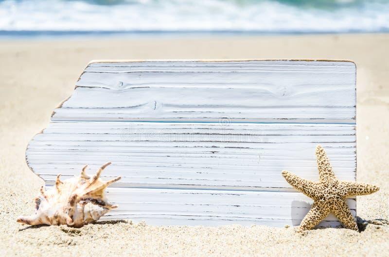 Белая деревянная доска с seashell и морские звёзды на песчаном пляже стоковая фотография rf