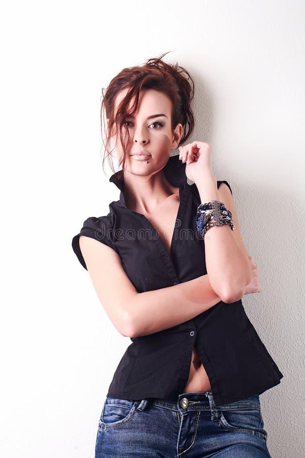 Белая женщина моды, коричневые красивые длинные волосы и глаза в черном жилете, голубые джинсы стоковое фото rf