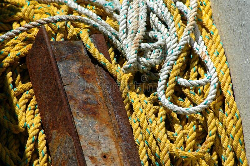 Белая и желтая веревочка и часть ржавого металла стоковое фото
