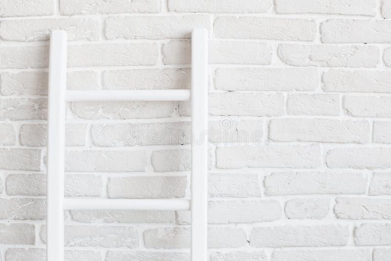 Белая кирпичная стена с лестницей стоковые фото