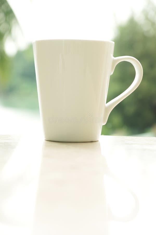 Белая кофейная чашка в утре стоковая фотография