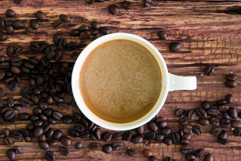 Белая кофейная чашка с зажаренными в духовке кофейными зернами на старой древесине стоковое изображение rf