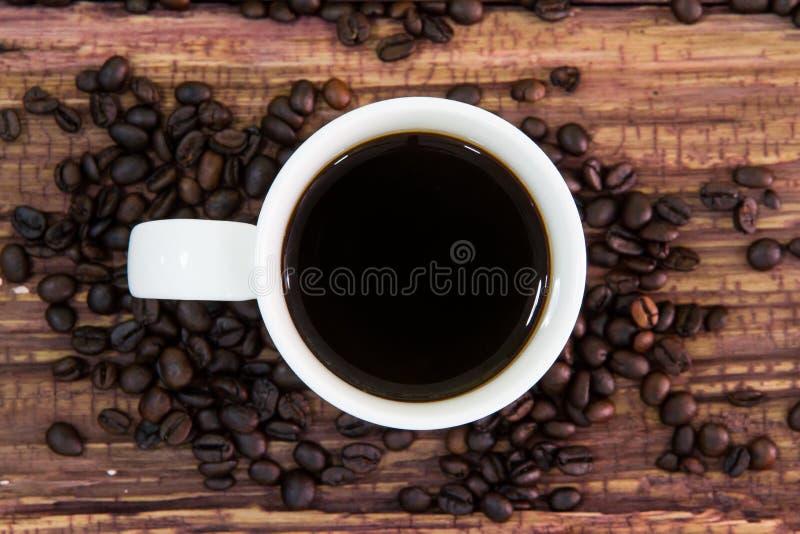 Белая кофейная чашка с зажаренными в духовке кофейными зернами на старой древесине стоковая фотография rf