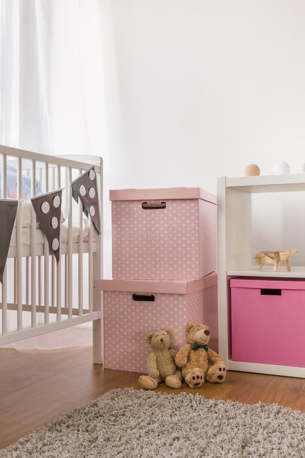 Белая кроватка и розовые коробки стоковые фото