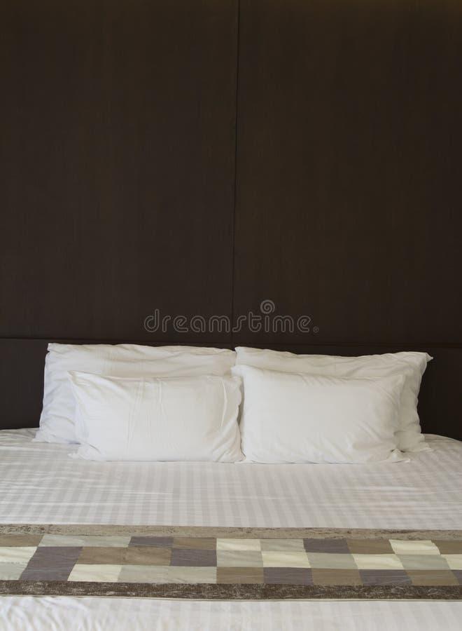 Белая кровать и деревянный Headboard стоковые фото