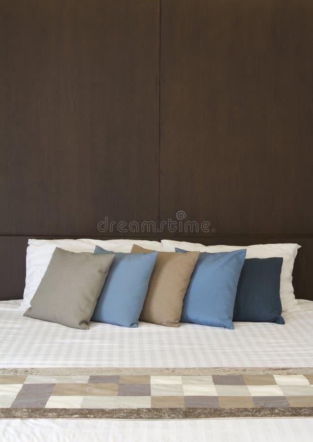 Белая кровать с Multi подушками цвета стоковые фото