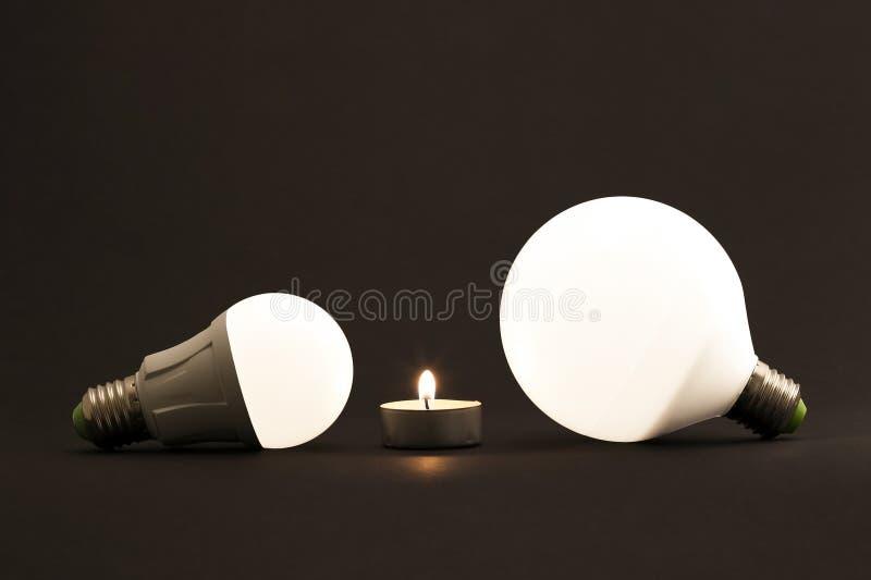 Белая маленькая свеча и электрические лампочки СИД на темной предпосылке C стоковая фотография
