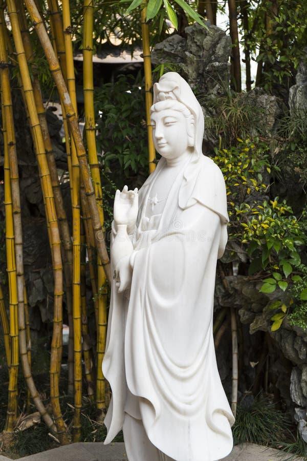 Белая мраморная статуя Будды Avalokitesvara в пруде лотоса, буддийской скульптуре Avalokiteshvara бодхисаттвы, богине пощады стоковая фотография rf