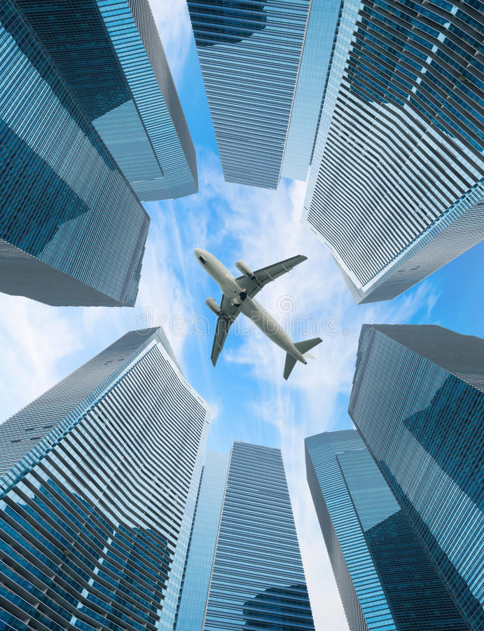 Белая муха самолета над современным городом стоковые фото