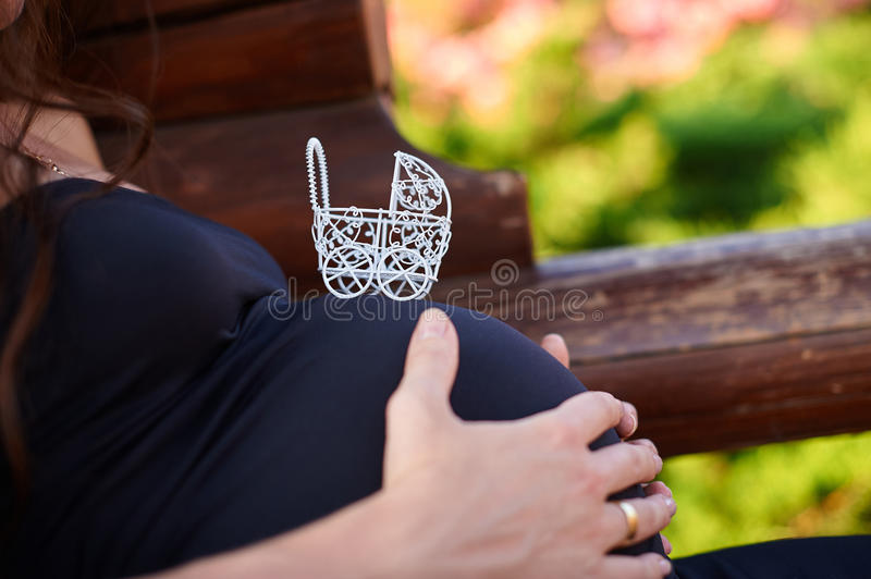 Белая прогулочная коляска игрушки на животе беременной женщины стоковые фото