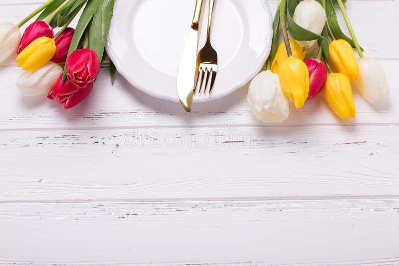 Белая плита, золотой столовый прибор и белые и красные тюльпаны цветут дальше стоковые изображения rf