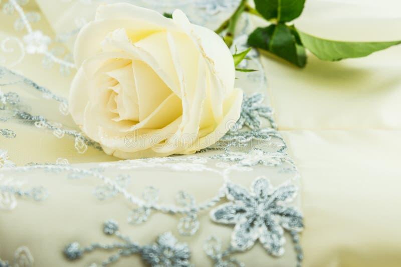 Белая роза на silk платье цвета слоновой кости свадьбы сатинировки стоковые изображения rf