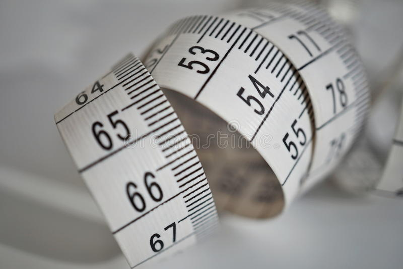 Белая рулетка длины ленты измеряя в метрах и сантиметрах на изолированной поверхности как символ инструмента используемый портное стоковая фотография
