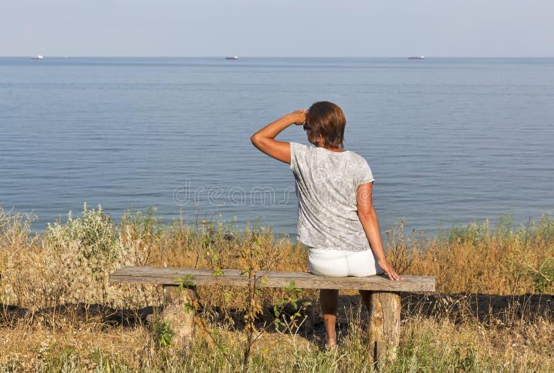Белая середина постарела женщина сидя на деревянной скамье с seascape стоковое изображение rf