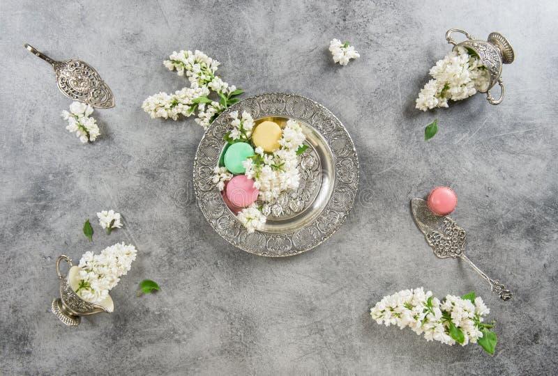 Белая сирень цветет торты macaroon Античные серебряные блюда стоковые изображения rf