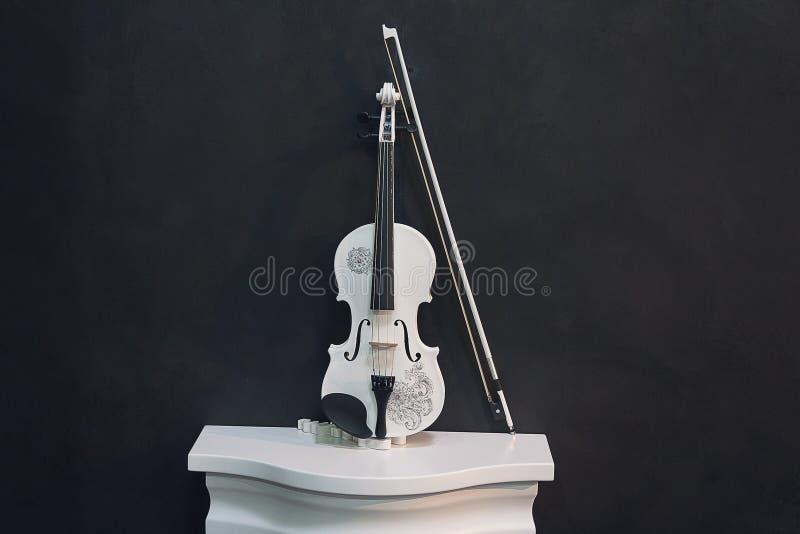 Белая скрипка на постаменте на черной предпосылке стоковая фотография rf