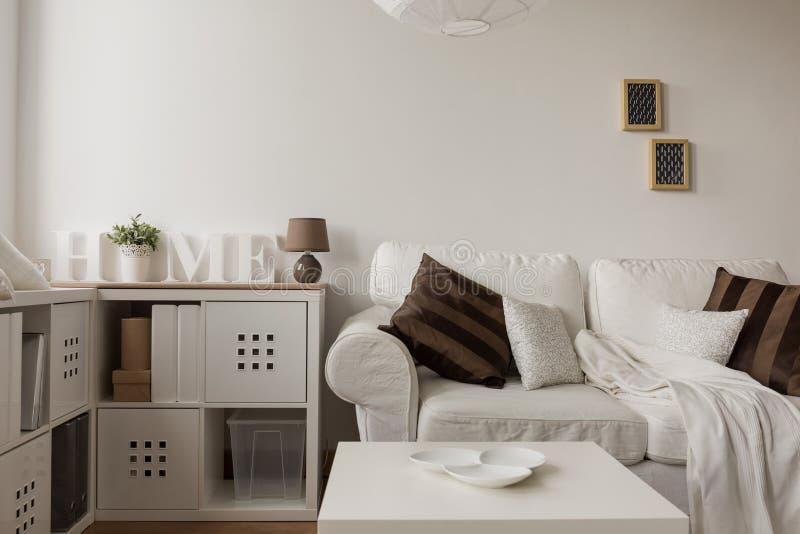 Белая софа и коричневые валики стоковая фотография rf