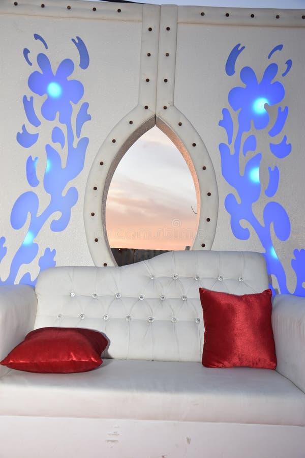 Белая софа свадьбы и 2 подушки шарлаха на этапе с небом захода солнца стоковое фото rf