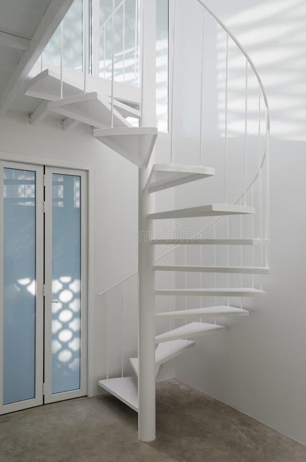 Белая спиральная лестница в современной комнате стоковые изображения