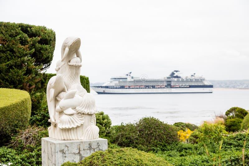 Белая статуя дельфина с туристическим судном стоковые фотографии rf