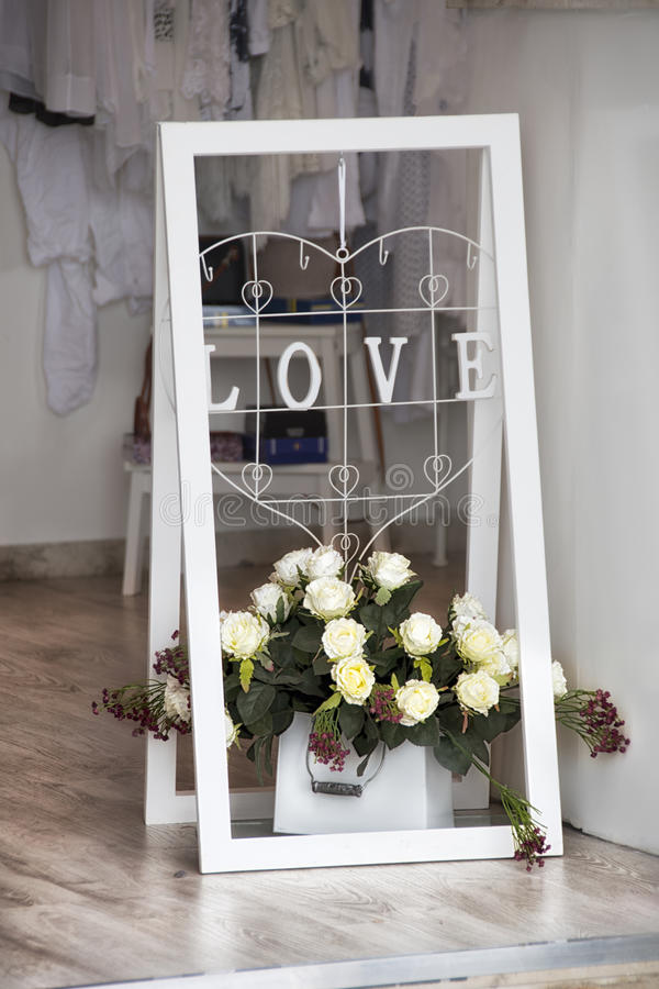 Белая стойка с цветками на входе магазина стоковое фото