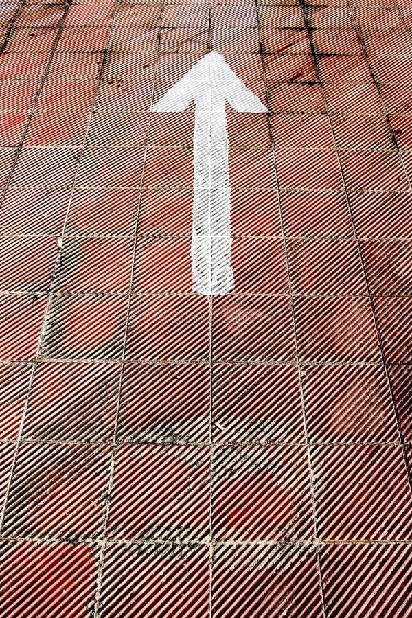 Белая стрелка покрашенная на поле автостоянки стоковая фотография