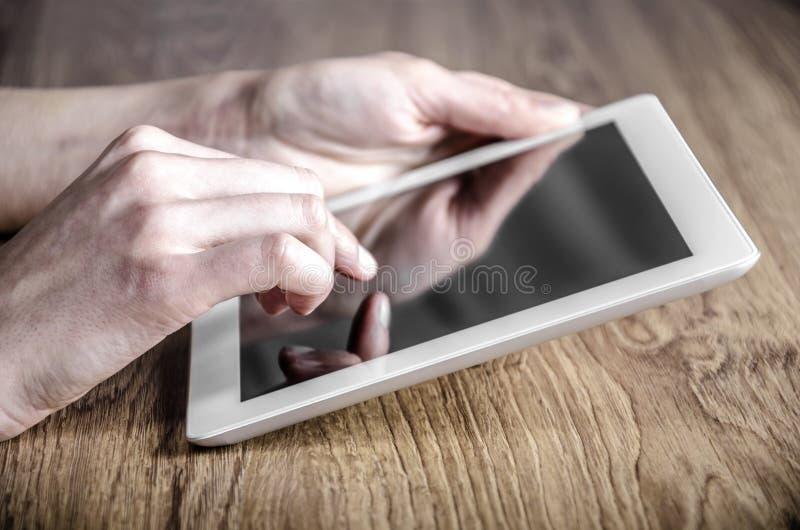 Белая таблетка с пустым экраном в руках на таблице стоковые изображения rf