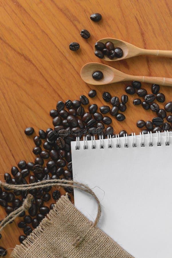 Белая тетрадь для вашего текста с дерюгой и кофейными зернами стоковые изображения