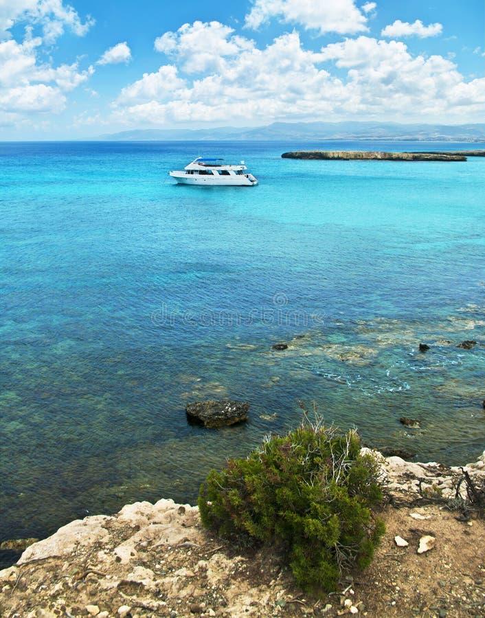 Белая туристская шлюпка в голубой лагуне стоковое изображение rf