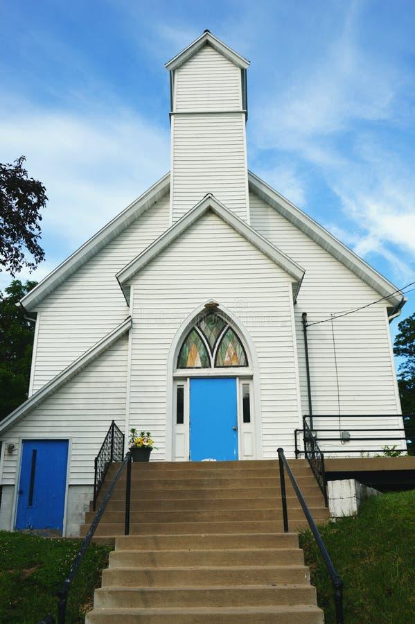Белая церковь с голубыми дверями и цветным стеклом стоковые изображения