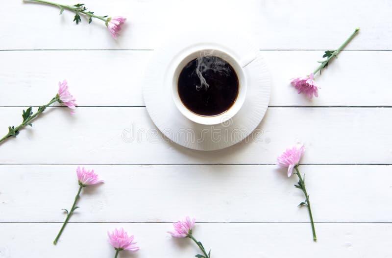 Белая чашка кофе с розовым цветком на белом деревянном столе в дне утра солнечном стоковое изображение