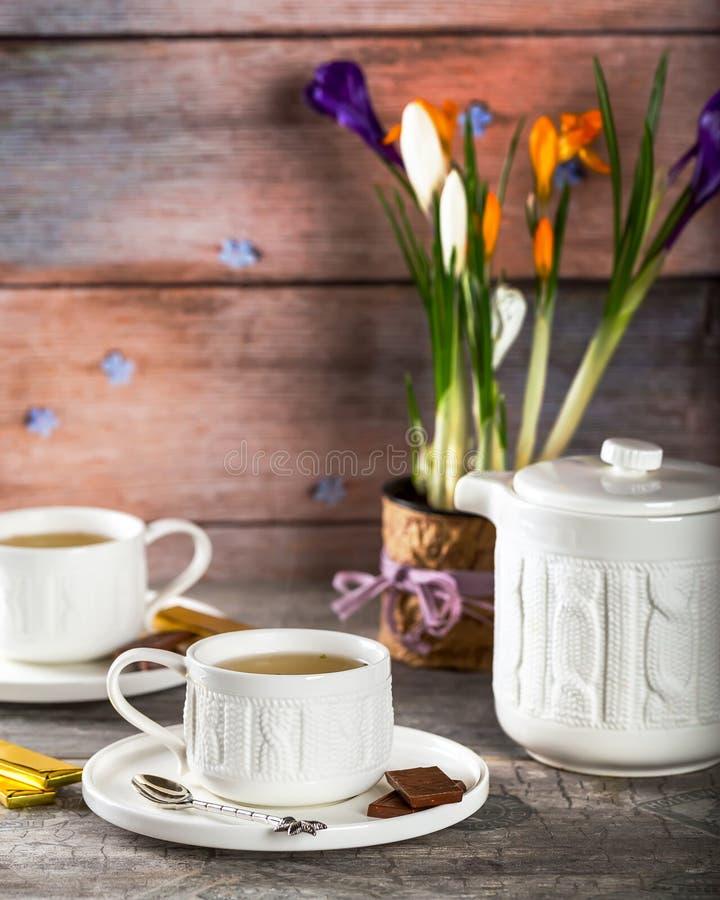 Белая чашка чаю на таблице Бак цветков на заднем плане стоковые изображения