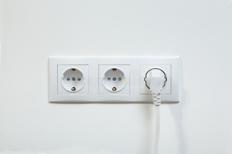 Белая штепсельная вилка заткнула внутри электрическое гнездо стоковые фотографии rf