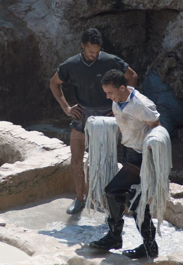 Белизна нося работника загорела тайники на традиционной кожаной дубильне стоковые изображения