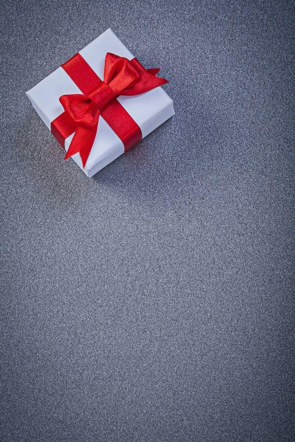 Белизна положила настоящий момент в коробку с красным узлом на сером поверхностном holi copyspace стоковое фото rf