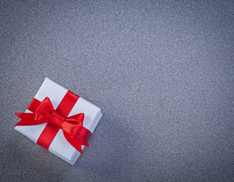 Белизна положила настоящий момент в коробку с смычком связанным красным цветом на серых поверхностных праздниках c стоковые изображения rf
