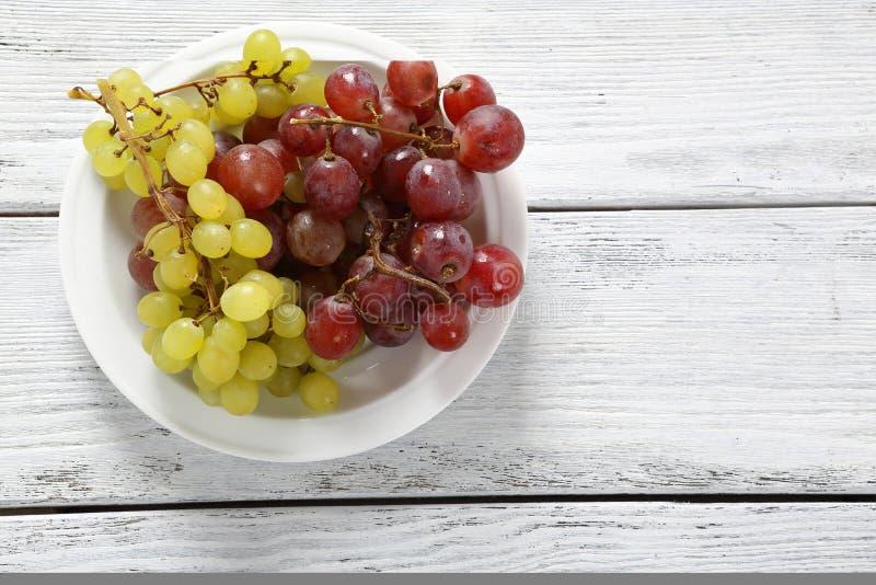 белизна плиты предпосылки изолированная виноградинами стоковое изображение rf