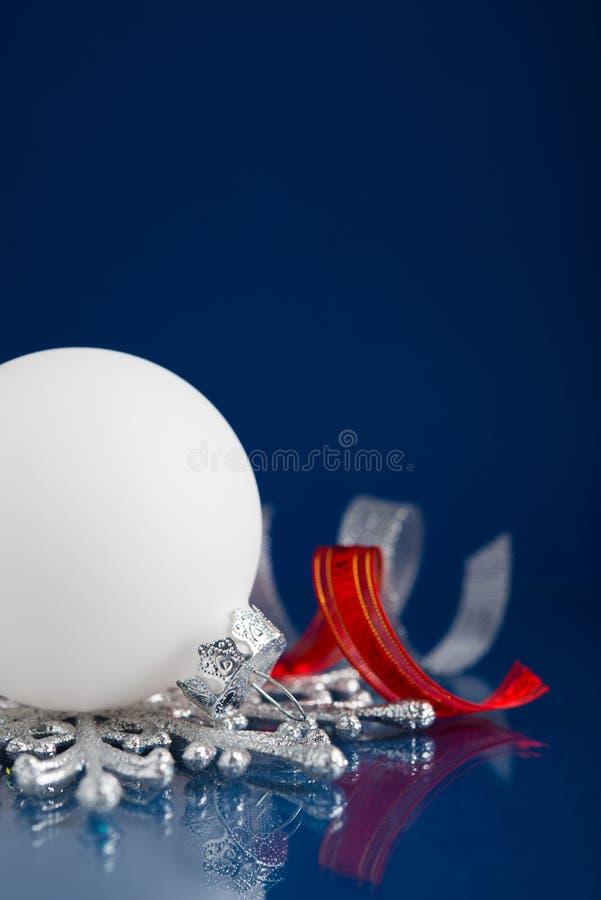 Белизна, серебр и красные орнаменты рождества на синей предпосылке стоковое изображение rf